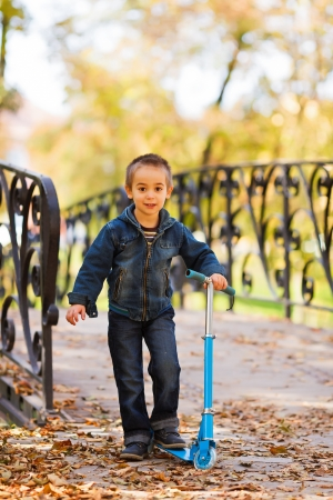 Excited little kid with his blue scooter playing in a park photo
