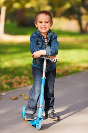 公園で彼のキック スクーターで小さな子供の笑顔