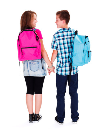 holding back: Happy teenage boy and girl holding hands - teen love concept Stock Photo