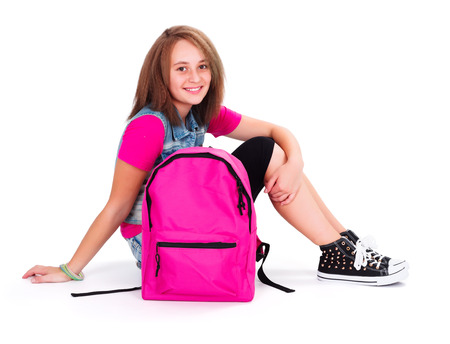 secondary schools: Teen girl in pink ready to go back to school - isolated image Stock Photo