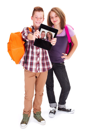 secondary: Teenager boy with girlfriend taking self portrait with tablet PC