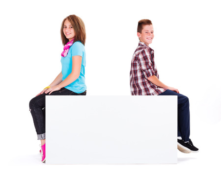 adolescents: Cute adolescents sitting on empty copy space placard Stock Photo