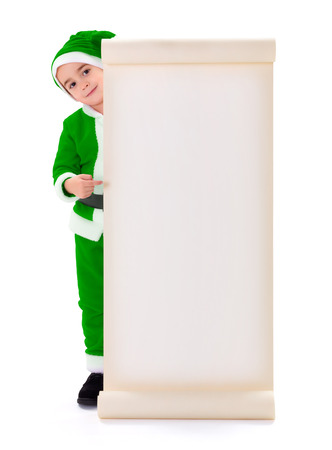 Little green Santa Claus boy, pointing at big blank wish list