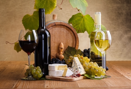 sliced cheese: Red wine with cheese and blue grape snack in front of small barrel