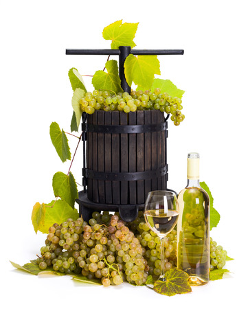 oenology: Traditional manual grape pressing utensil with wine and white grape bunch Stock Photo
