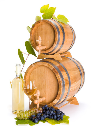 White wine in front of stacked barrels, grape clusters and leaves photo