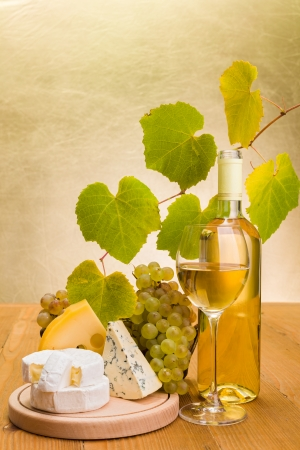 White wine in bottle and glass with grapes, camembert, emmentaler and blue cheese snack, grape leaves decoration photo