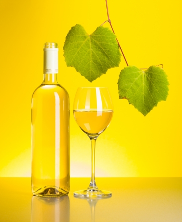 Bottle and glass of white wine with grape leaves on yellow  photo
