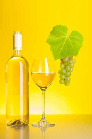 Bottle and glass of white wine with grape cluster on yellow  photo