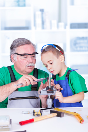 Grandfather teaching grandchild measuring with vernier caliper Stock Photo