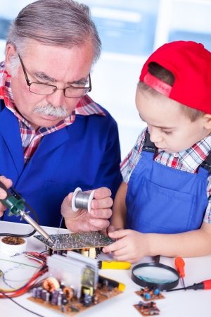 soldering: Grandfather showing PCB soldering to grandchild (Shallow DOF, only the old man in focus) Stock Photo