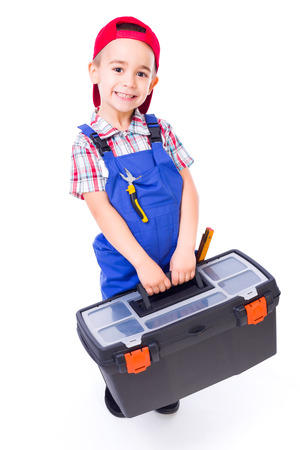 Happy little handyman boy carrying big toolbox and pliers in pocket photo