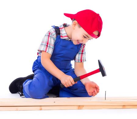 Little carpenter hitting nail into fir wood board