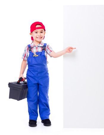 Little handyman with toolbox, pointing at big, empty advertising panel photo