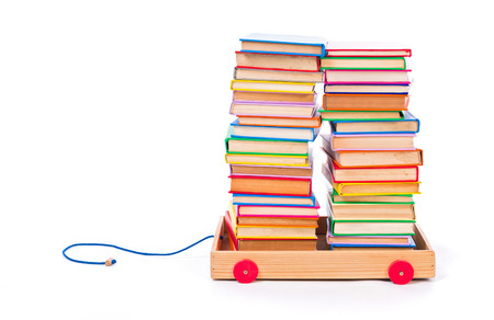 stacked books: Little toy cart full of stacked, colorful books