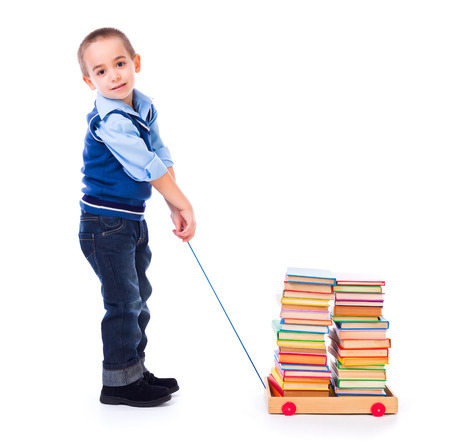 pull toy: Niño pequeño que tira del carro de juguete lleno de libros de colores
