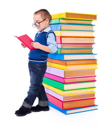 niños leyendo: Poco sabia lectura de libros muchacho cerca gran pila de libros de colores Foto de archivo