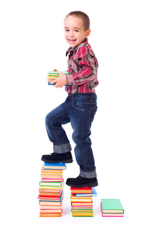 Little boy climbing on stairs made of colorful books photo