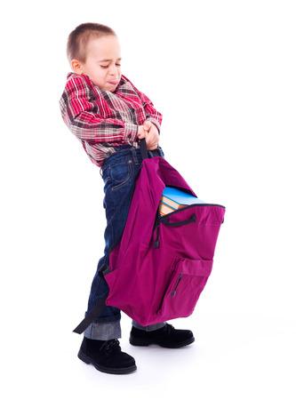 Little boy lifting big, heavy schoolbag full of books