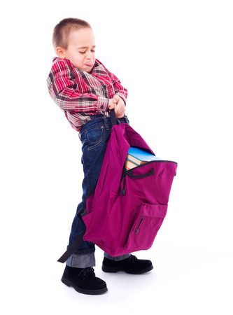 heavy lifting: Little boy lifting big, heavy schoolbag full of books