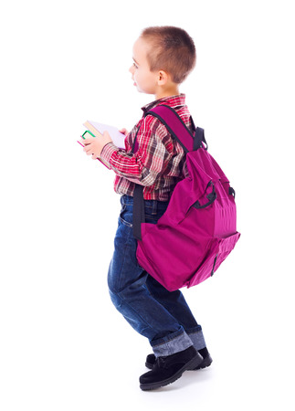 Little boy carrying big, heavy schoolbag full of books photo