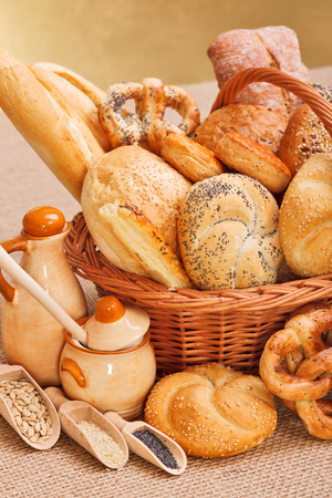 Fresh bakery products in wicker basket, various ingredients decoration