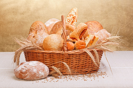 Various fresh bakery products in wicker basket, wheat decoration