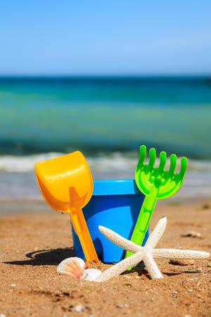 beach toys: Toy shovel, rake and bucket on beach