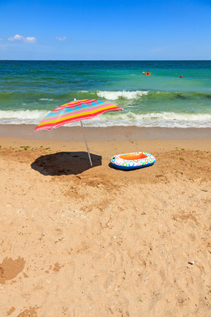 beach toys: Colorful beach umbrella and inflatable toy boat at sea Stock Photo