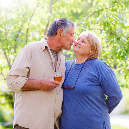 married couples: Middle aged affectionate married couple in garden, man holding wine glass