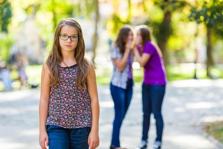 discriminacion: Niñas envidiosas que discriminan a su novia por hablar detrás de ella Foto de archivo