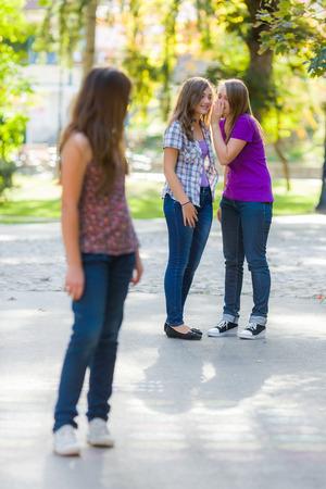 Envious girls talking behind her girlfriend in park