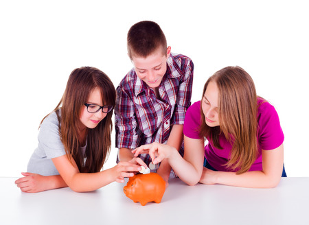 Three teenagers collecting money together for their future business. They put coins in piggy bank Banco de Imagens