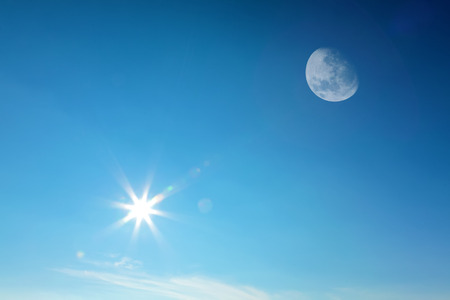 sun lit: Moon and sun together on the daytime blue sky (Composite image).