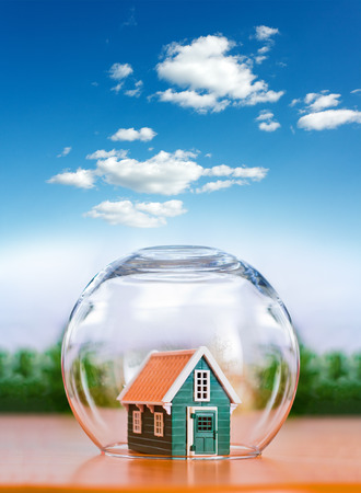 Insured house protected in glass sphere, under the cloudy bright sky