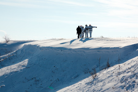 hunters: Group of hunters walking on the field in winter Stock Photo