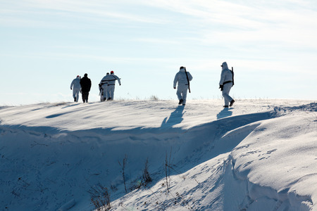 hunter's: Group of hunters walking on the field in winter Stock Photo