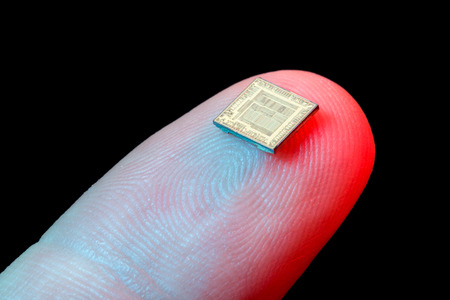 microchip: Silicon micro chip on human fingers tip