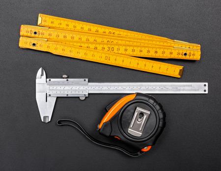cintas metricas: Herramientas en el fondo negro de medici�n: regla, pinza y cinta en negro Foto de archivo
