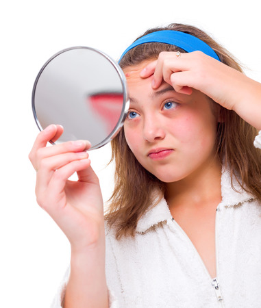 pimples: Teen girl examine her pimples in the mirror