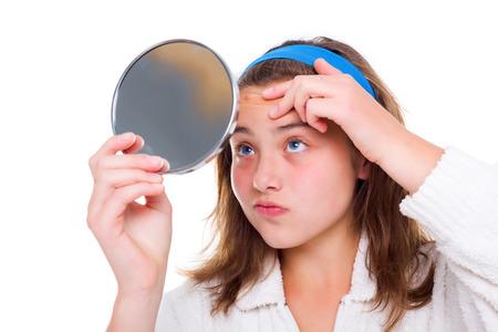ティーンエイ ジャーの女の子が鏡の中の彼女のにきびを調べる