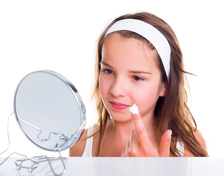 girl care: Teen girl looking in the mirror and creaming her face