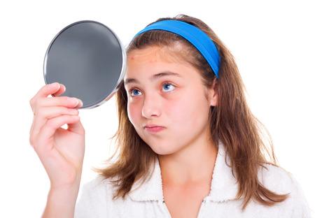 十代の少女は鏡の中の彼女のにきびを調べる