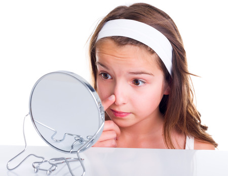 beautiful teen girl: Teen girl searching for pimples, looking in the mirror