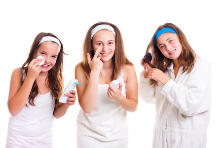 primp: Teen girls primping using tonic lotion, cream and hair brush Stock Photo
