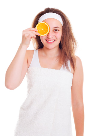 primp: Teenager girl covering her eye with orange slice