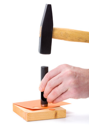 hole puncher: Human hand making holes using hole puncher and hammer Stock Photo