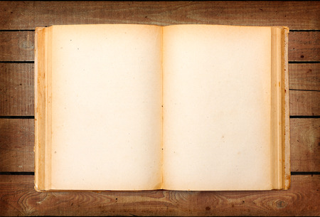 Top view of old book with empty yellowed pages on wooden background