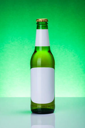 green beer bottle: Green beer bottle with blank labels on elegant, backlit background