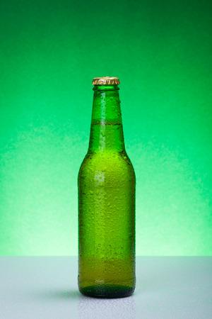 green beer bottle: Wet green beer bottle on backlit background
